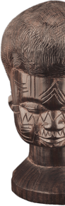 Dark brown carved wood figure of a human head and neck with closed eyes and geometric tattoo designs on the face