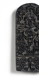 A black rectangular stamp that is rounded on top and has detailed Christian imagery of a church, angels, and other figures carved into it.