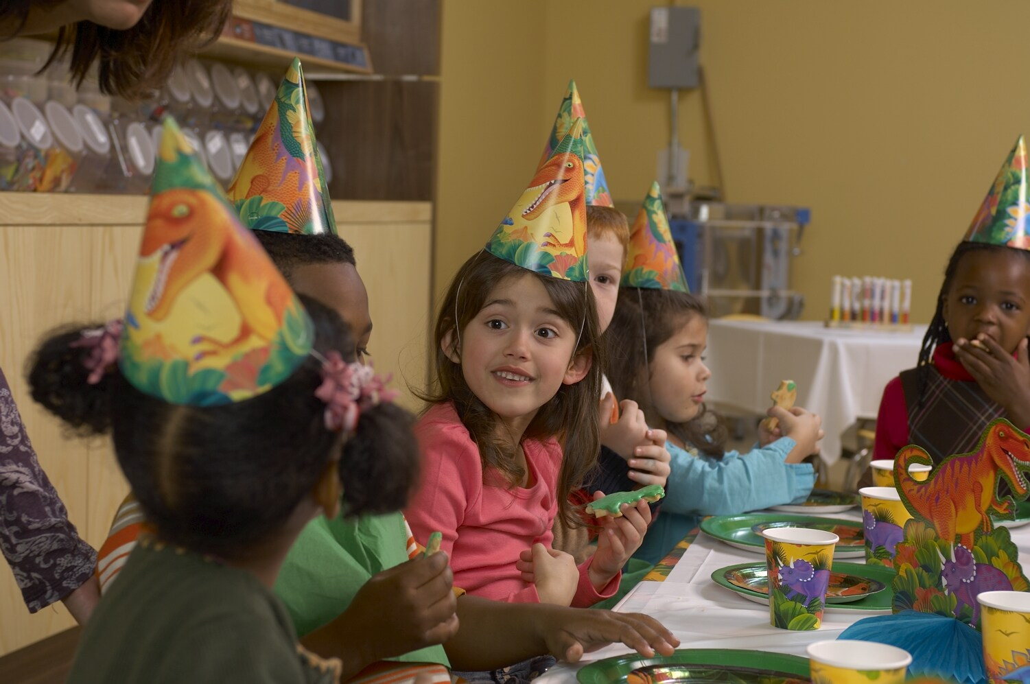 A group of children wearing party hats, seated around a table with party decoration.