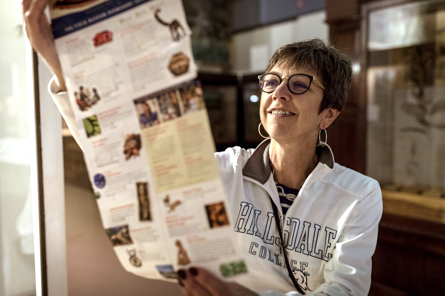 A woman wearing glasses reads a map that's she's unfolded in front of her.