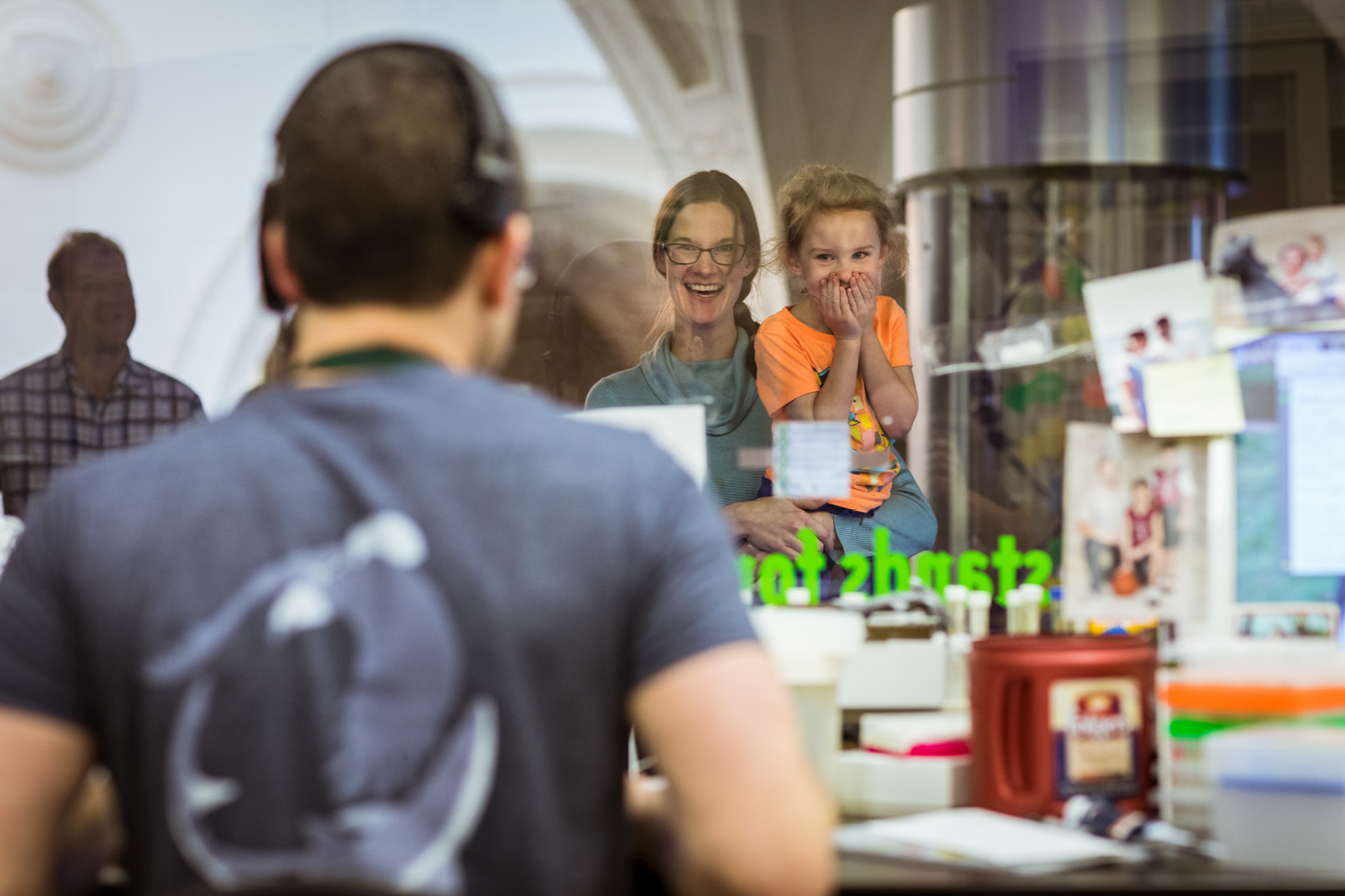 DNA researcher stands facing the glass between the Daniel F. and Ada L. Rice DNA Discovery Center and the Pritzker Laboratory for Evolutionary Biology and Molecular Systematics. A woman holds a girl with an excited look on her face up to the glass to see