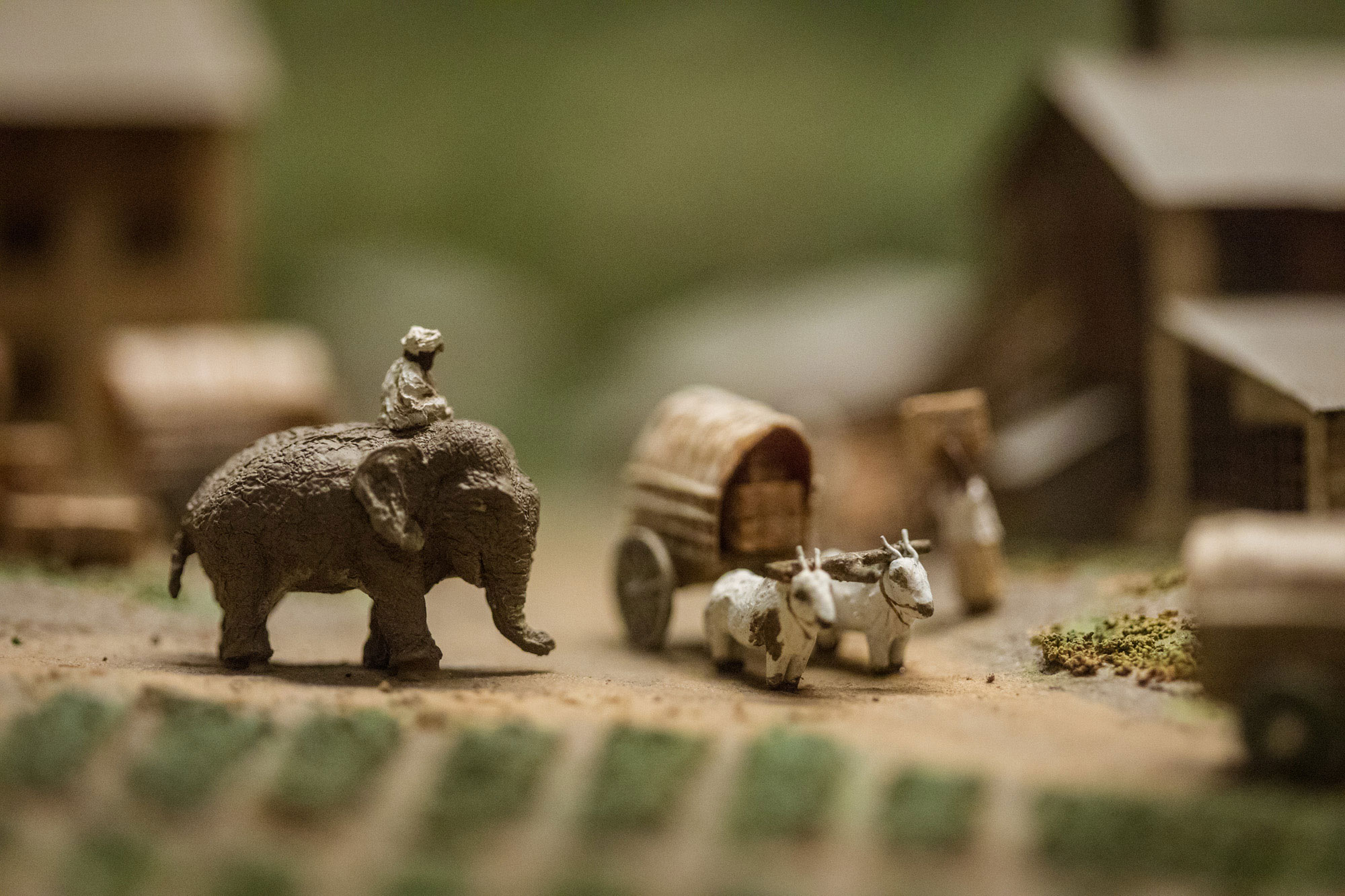 Close-up view of a diorama featuring a man riding an elephant and two goats pulling a wagon.
