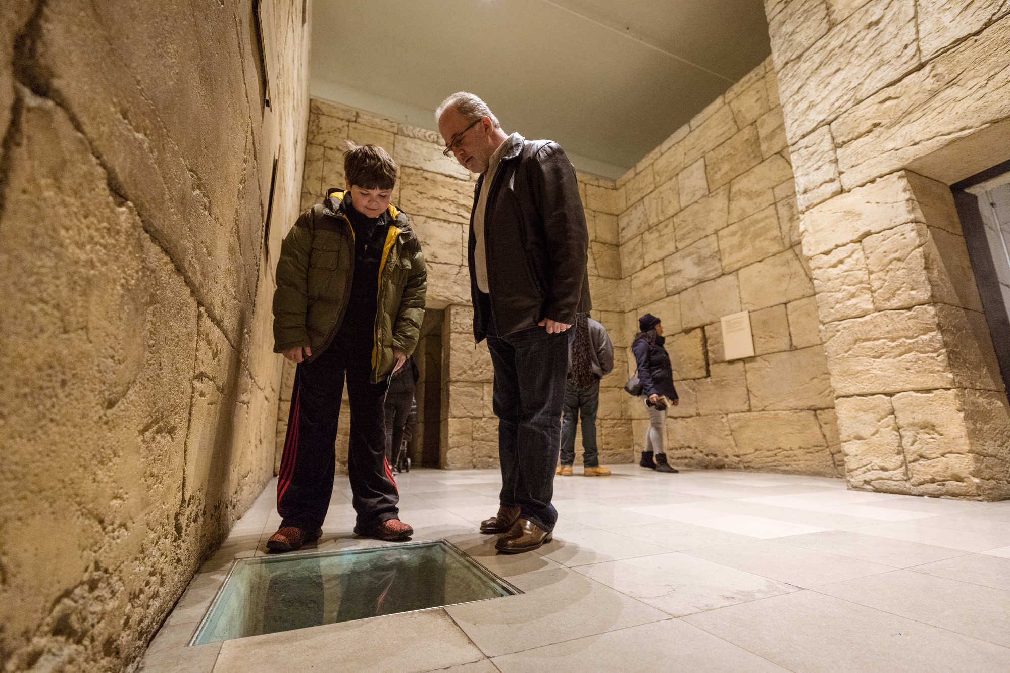 Standing in the ancient Egyptian tomb in the Inside Ancient Egypt exhibition, an adult and child look down at a glass-covered opening in the floor.