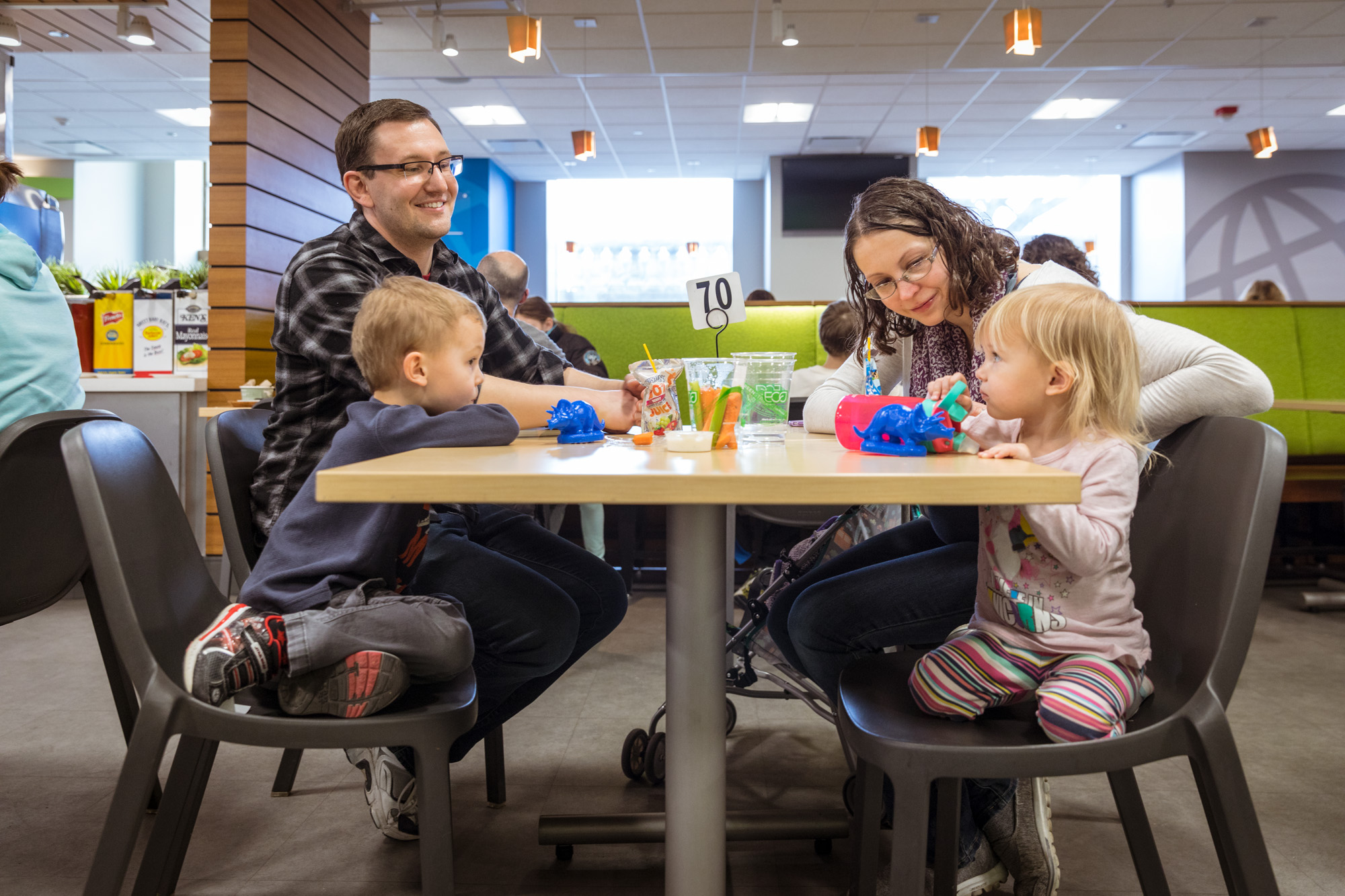 A family of four sits at a table in the Explorer Cafe. Parents smile and look on as a young boy and girl share a cup of vegetables and juice. Two blue plastic triceratops are also on the table.