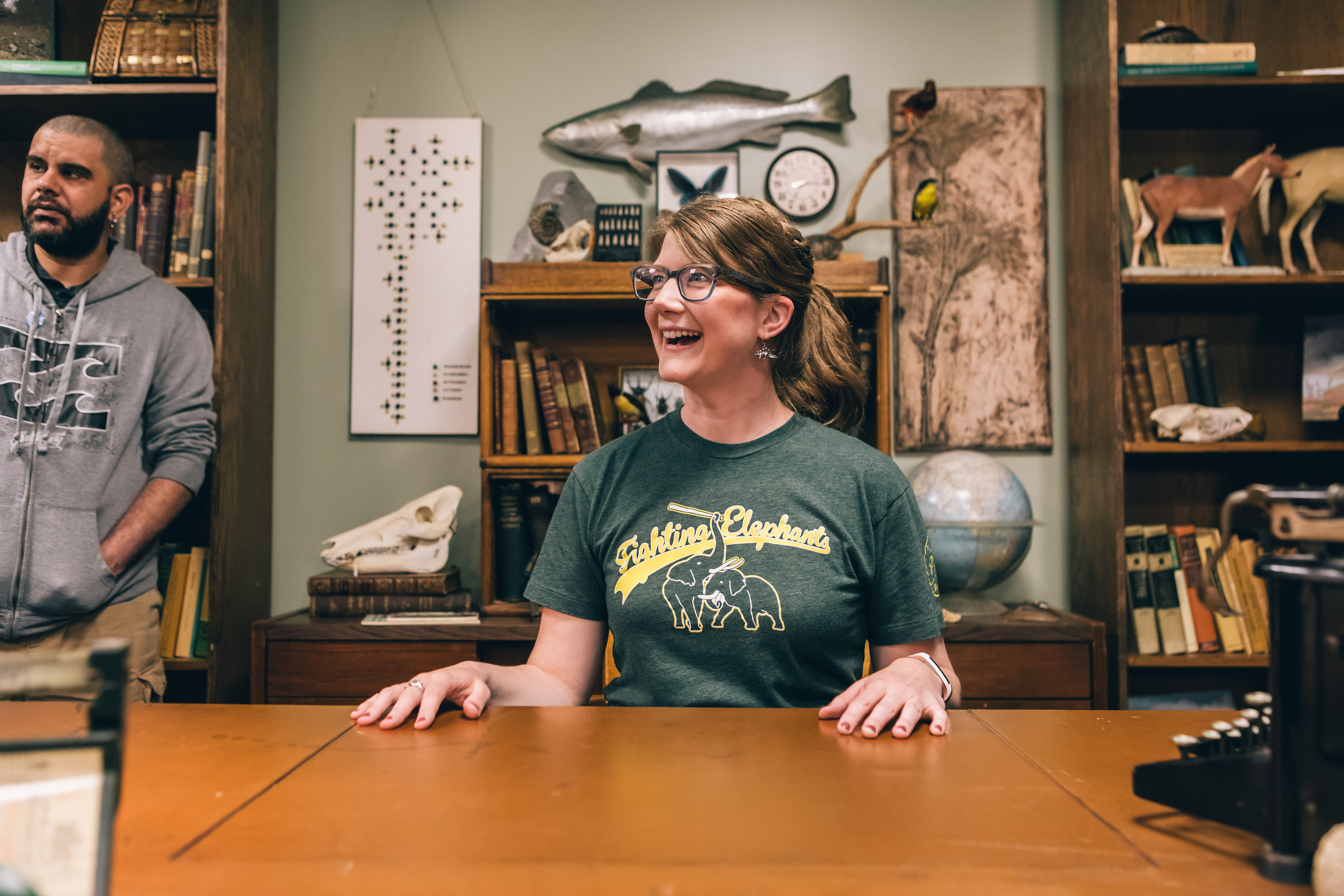 Emily Graslie smiles and looks to her right, while sitting at a desk. Books and specimens are visible in the background.