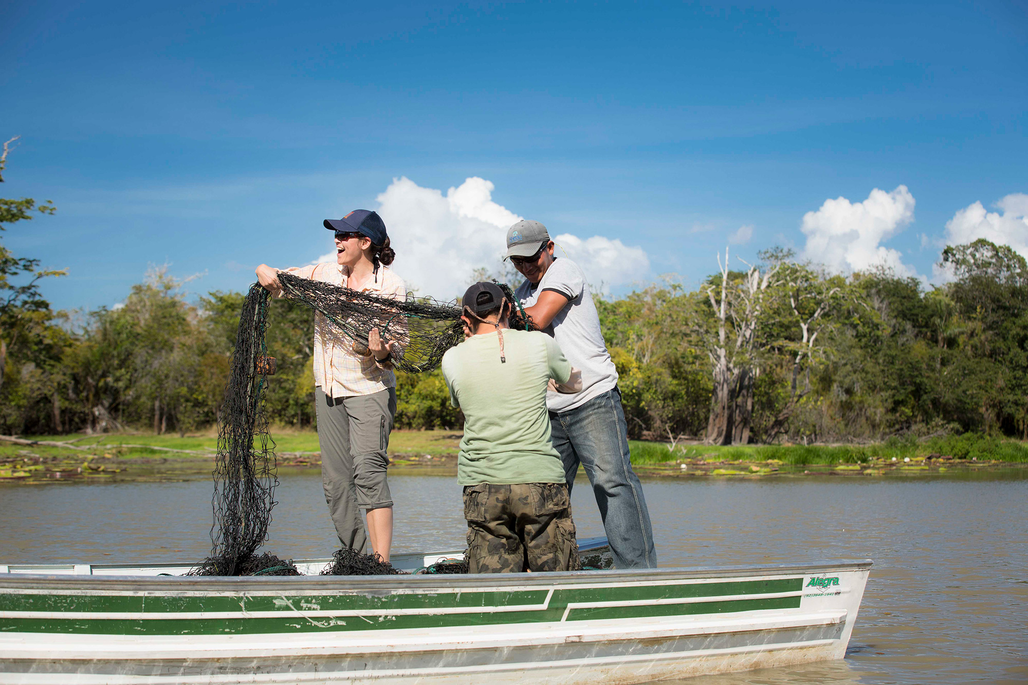 Three scientists prepare a fishing net from a boat while out conducting fieldwork in Guyana.