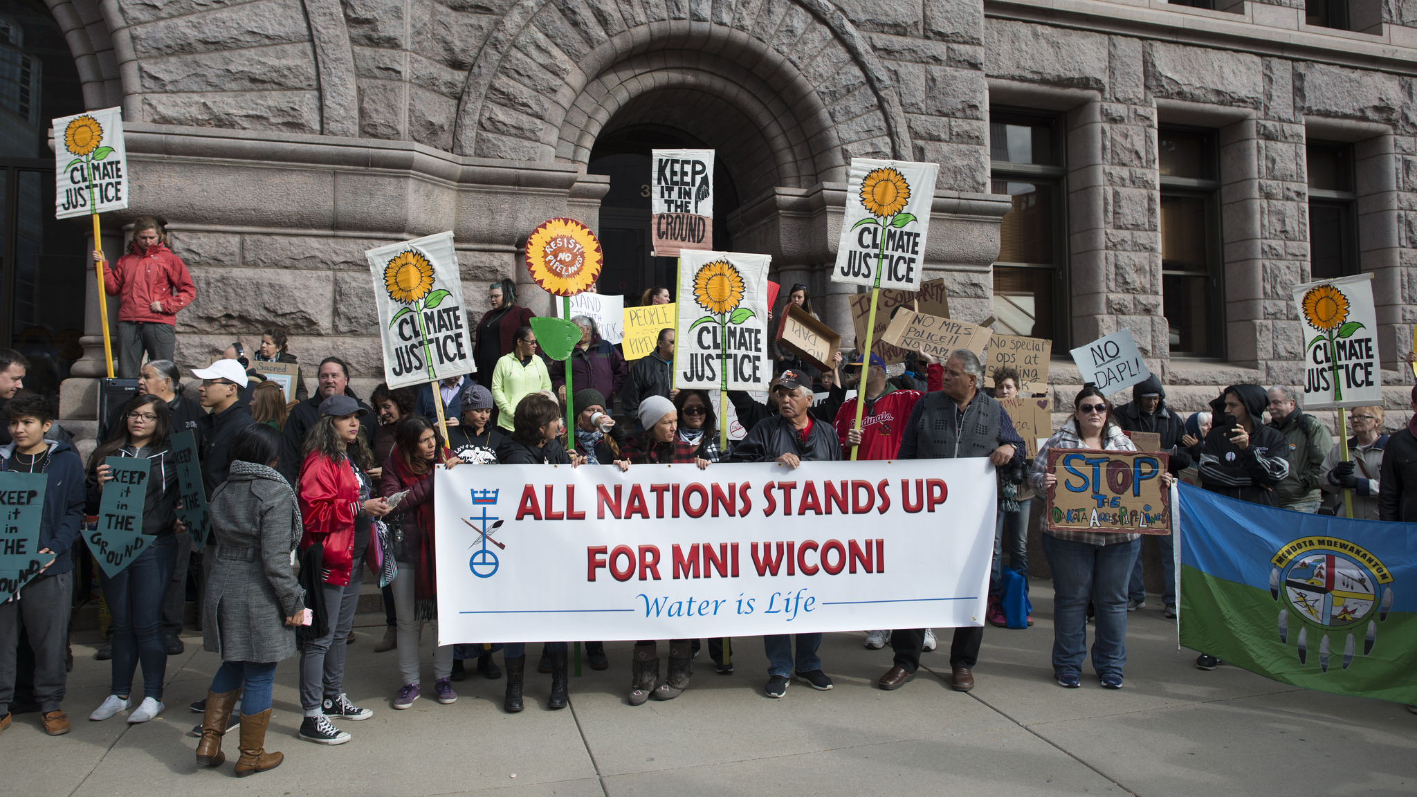 "Group of people holding signs in protest outside a building, with a large banner that reads ""All Nations Stands Up for Mni Wiconi, Water is Life"""