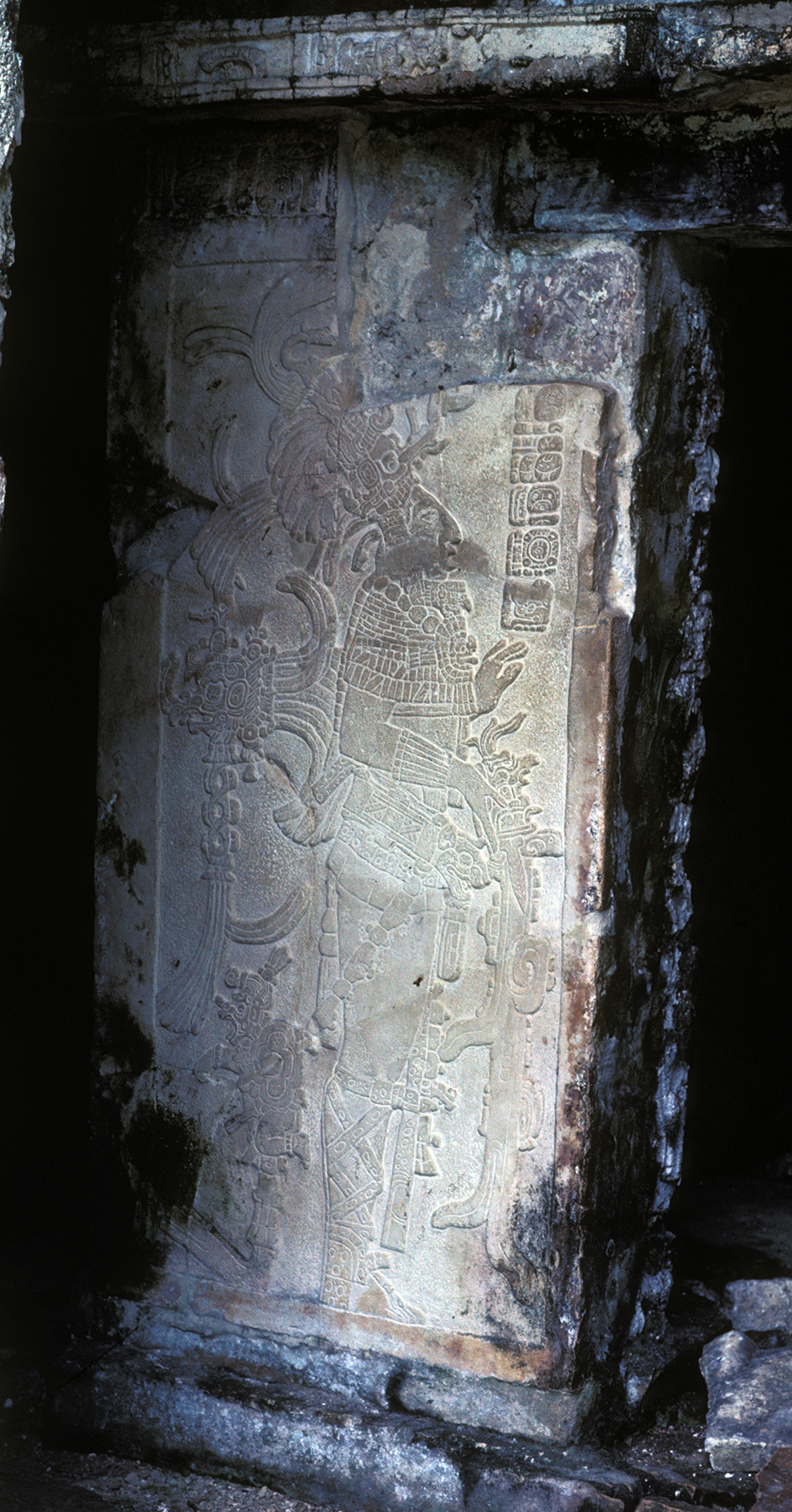 A tall vertical stone with detailed carving of a person with an elaborate headdress and holding what appears to be a knife