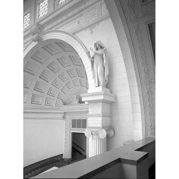 Architectural view the southwest upper corner of Stanley Field Hall, featuring the coffered panel ceiling and a statue of a female figure holding a magnifying glass, representing Research, by artist Henry Hering.