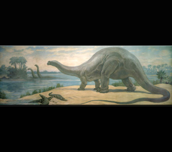 An apotasaurus standing on a sandy ground, while three much smaller crocodile-like creatures stand below. Two other long-necked dinosaurs are in the water in the background, reaching their heads toward tall trees.