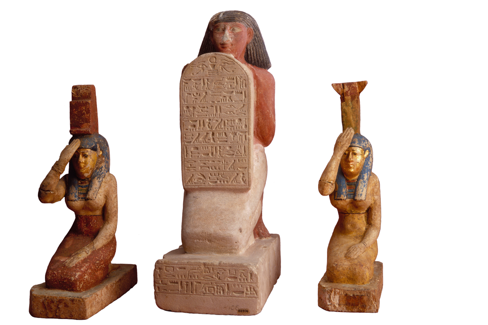 Three small Egyptian statues, the center holding a stone hieroglyphic text.