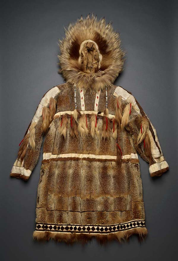 A brown fur and animal skin coat, decorated with beads and red yarn