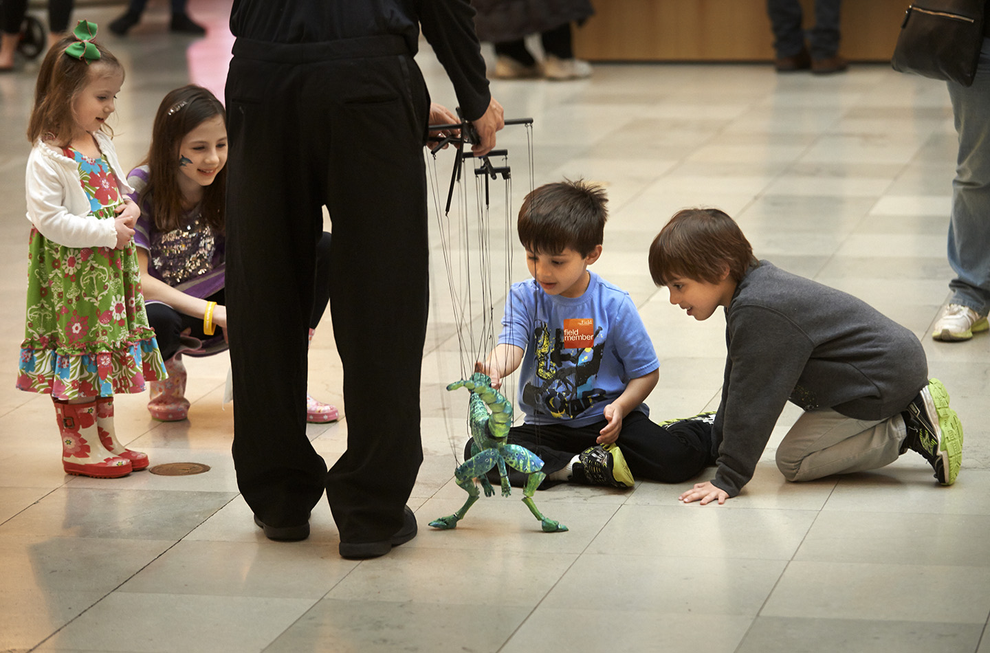 Young children gather around a puppeteer, who animates a dragon marionette.