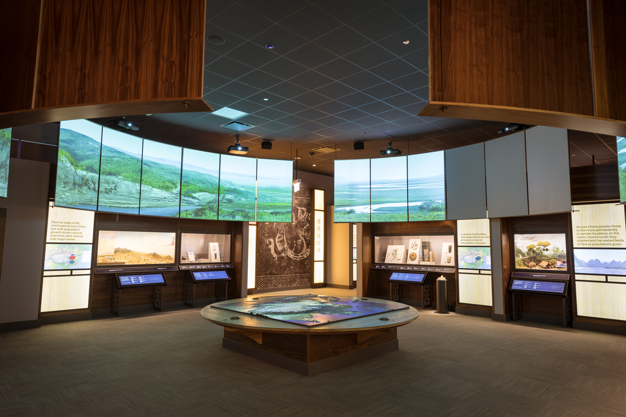 The first gallery of the Cyrus Tang Hall of China, with map table in the foreground and a large circle of video screens above the exhibition display cases.