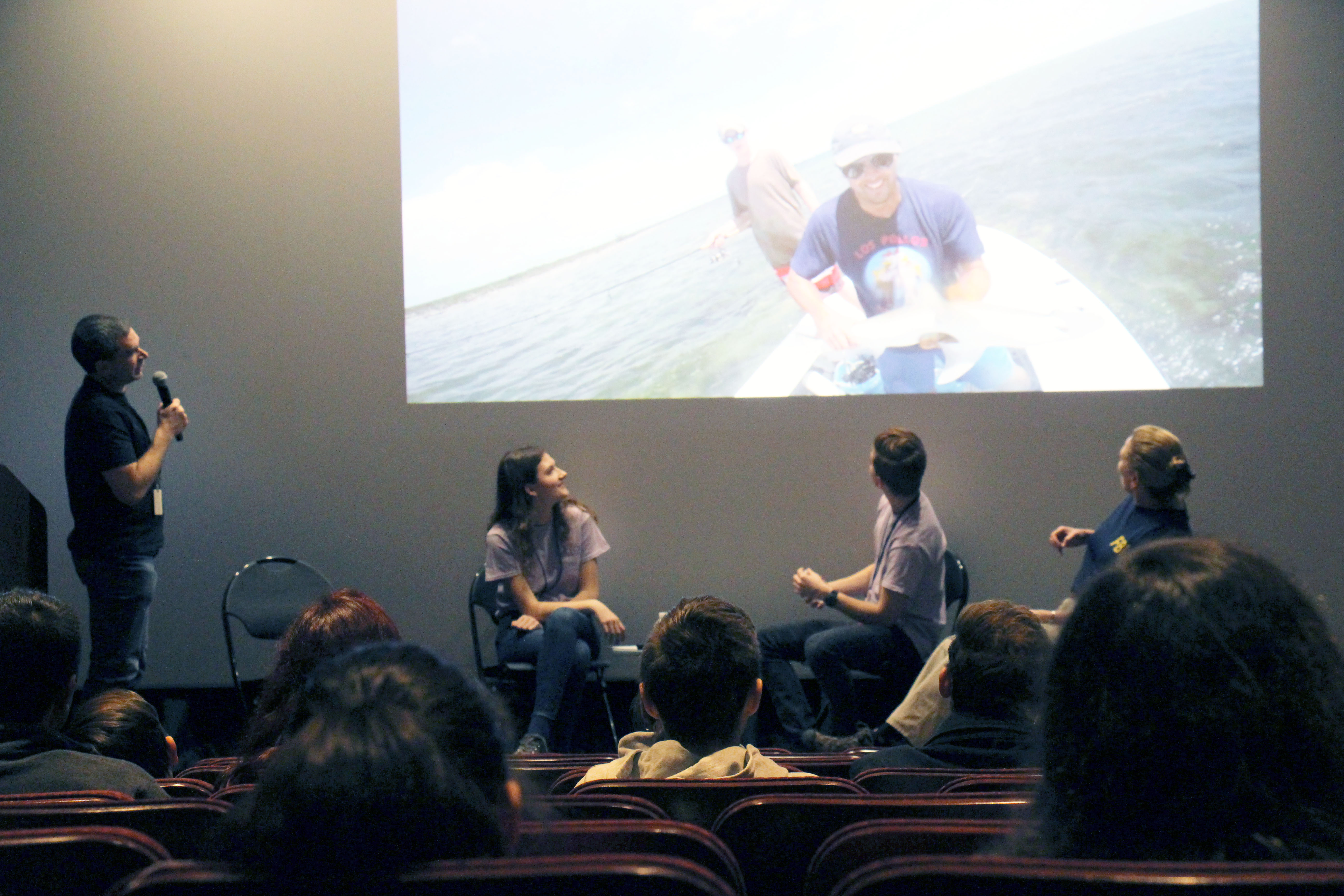 The curioCITY panel—two teens and two adults—sit and stand on stage. All look behind them to view a footage of two adults in a boat.