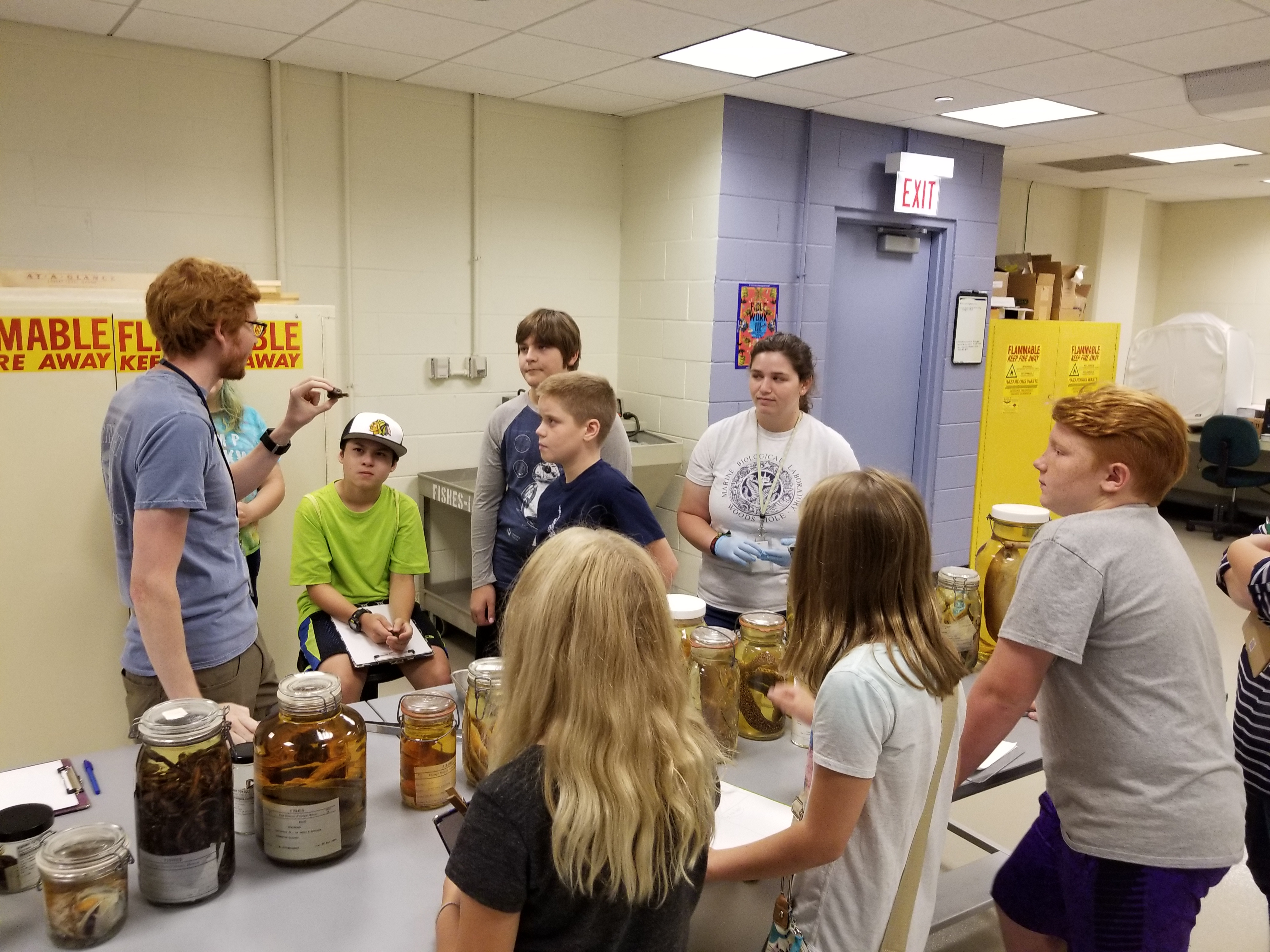 A group of students gather around an educator holding a small specimen. Jars on a table hold various specimens in liquid.