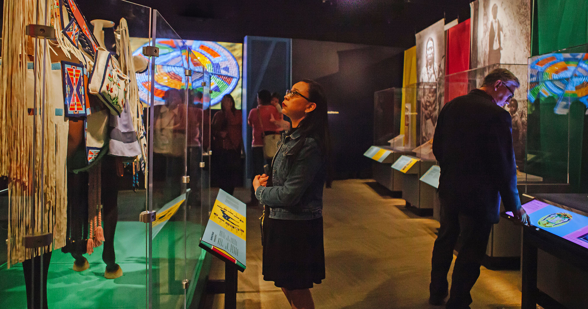 Josee Starr looks at regalia inside a display case in the exhibition Apsáalooke Women and Warriors. A screen in the background shows brightly colored beadwork.