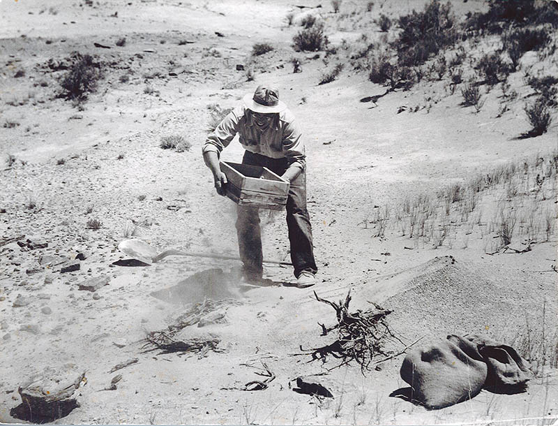 Black and white photo of a man wearing a hat and sifting sand through a screen