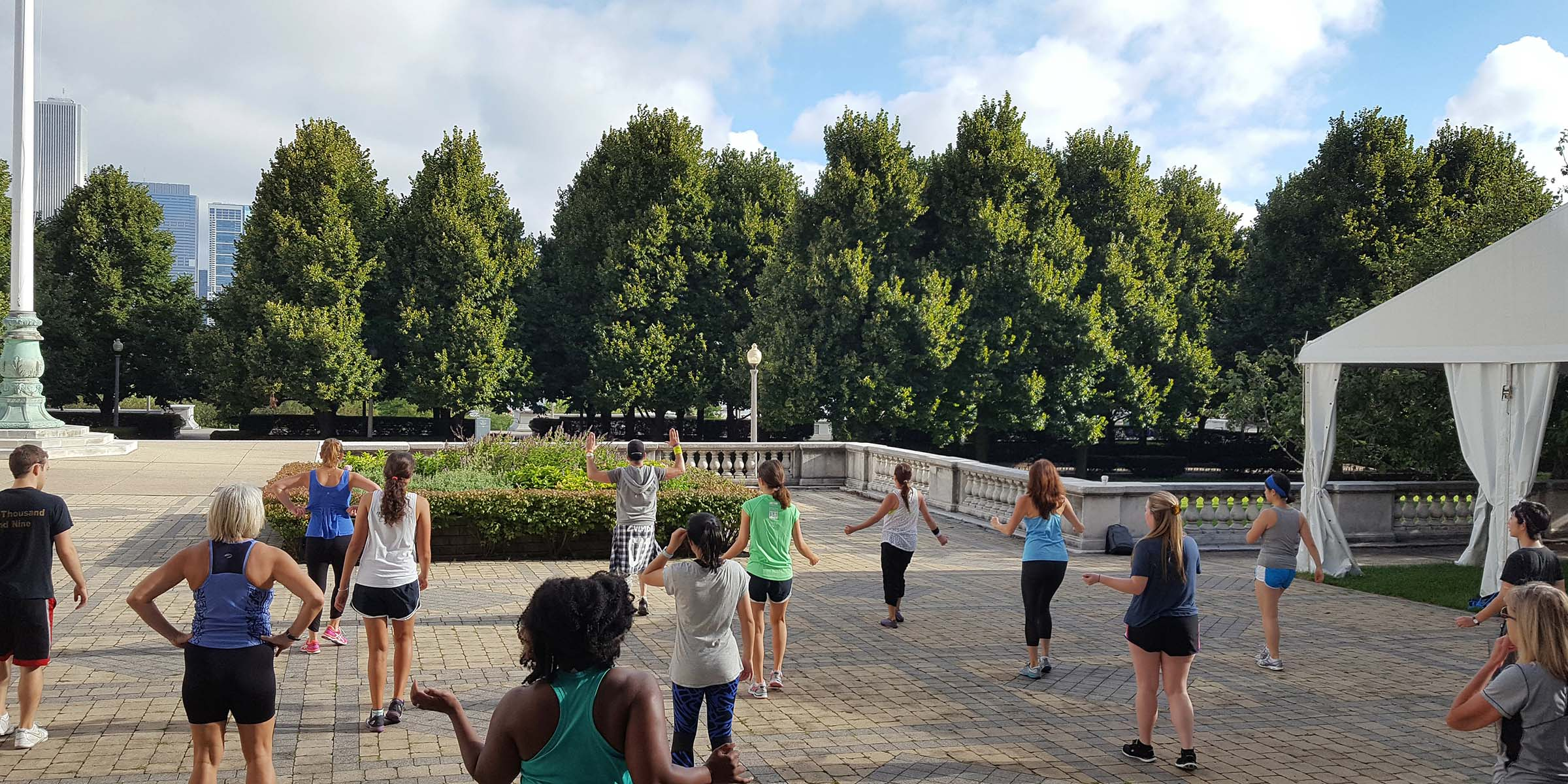A group of people doing a workout outdoors on a patio with a row of tall trees in the background