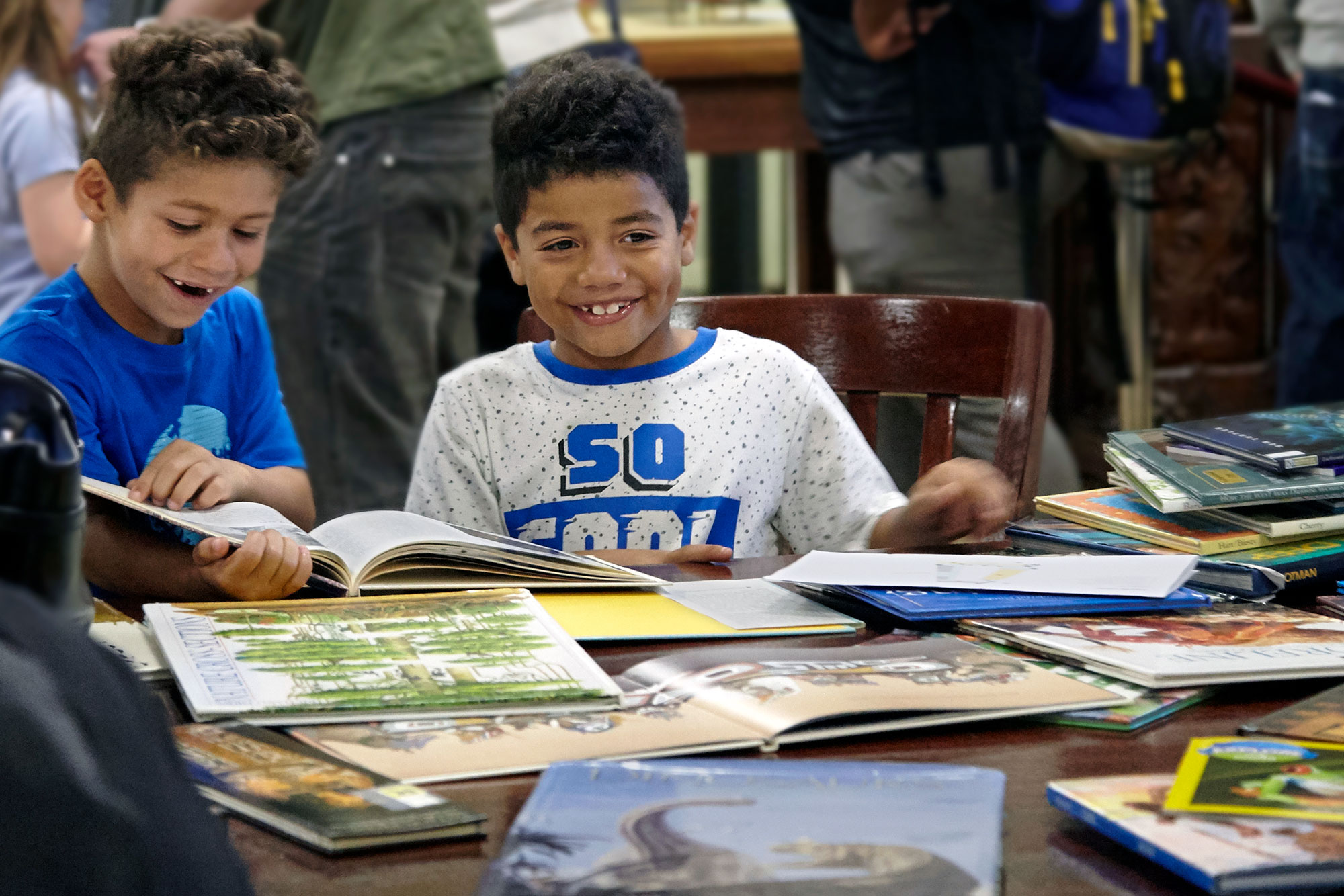 Two children seated at a table look at picture books.