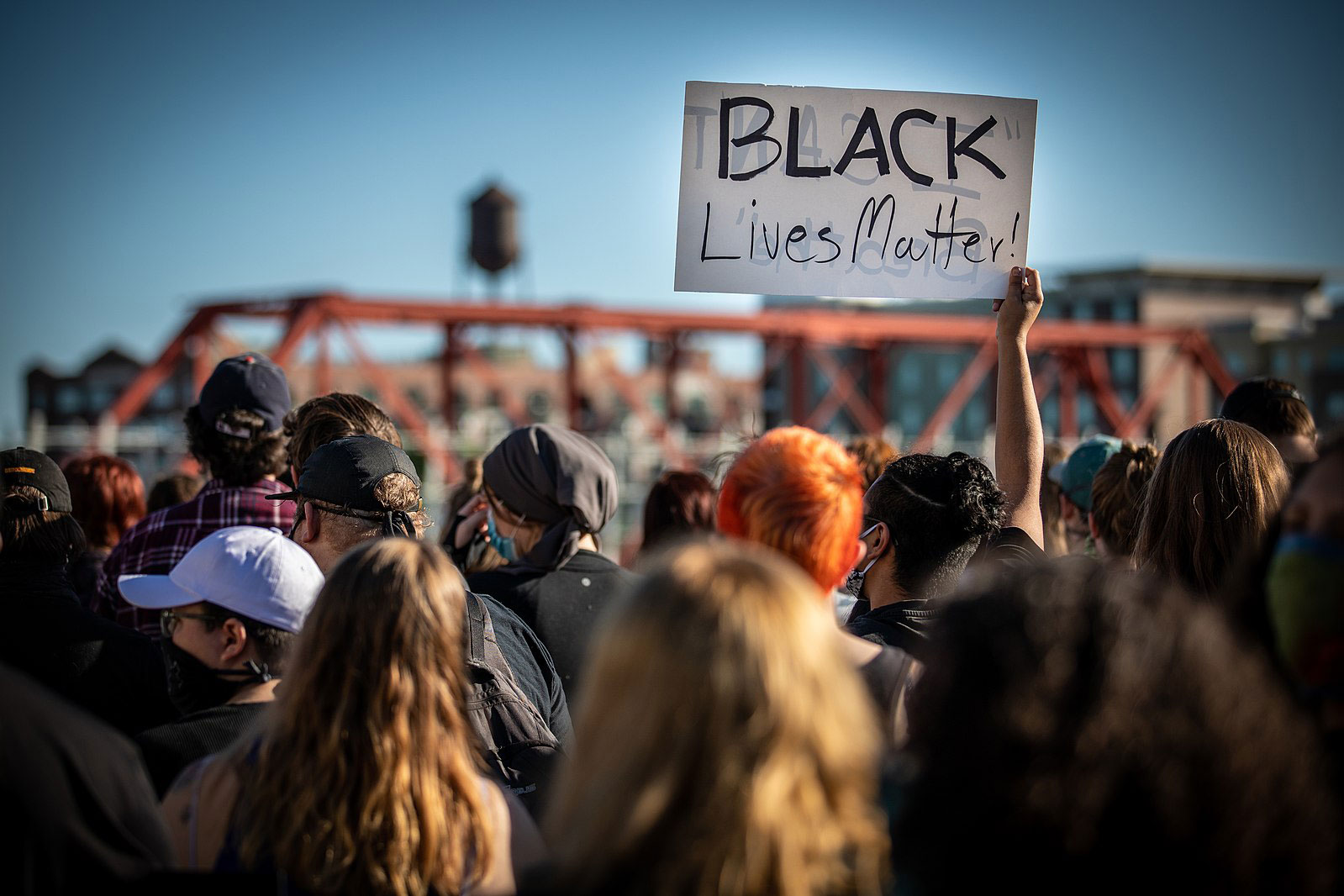 The backs of heads of many people gathered together. One person holds up a sign that reads,