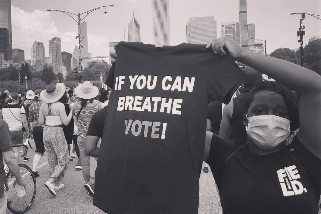 """Ylanda Wilhite at a protest in downtown Chicago. She wears a facemask and a Field Museum shirt while holding up a t-shirt that reads, """"If you can breathe, vote!"""""""