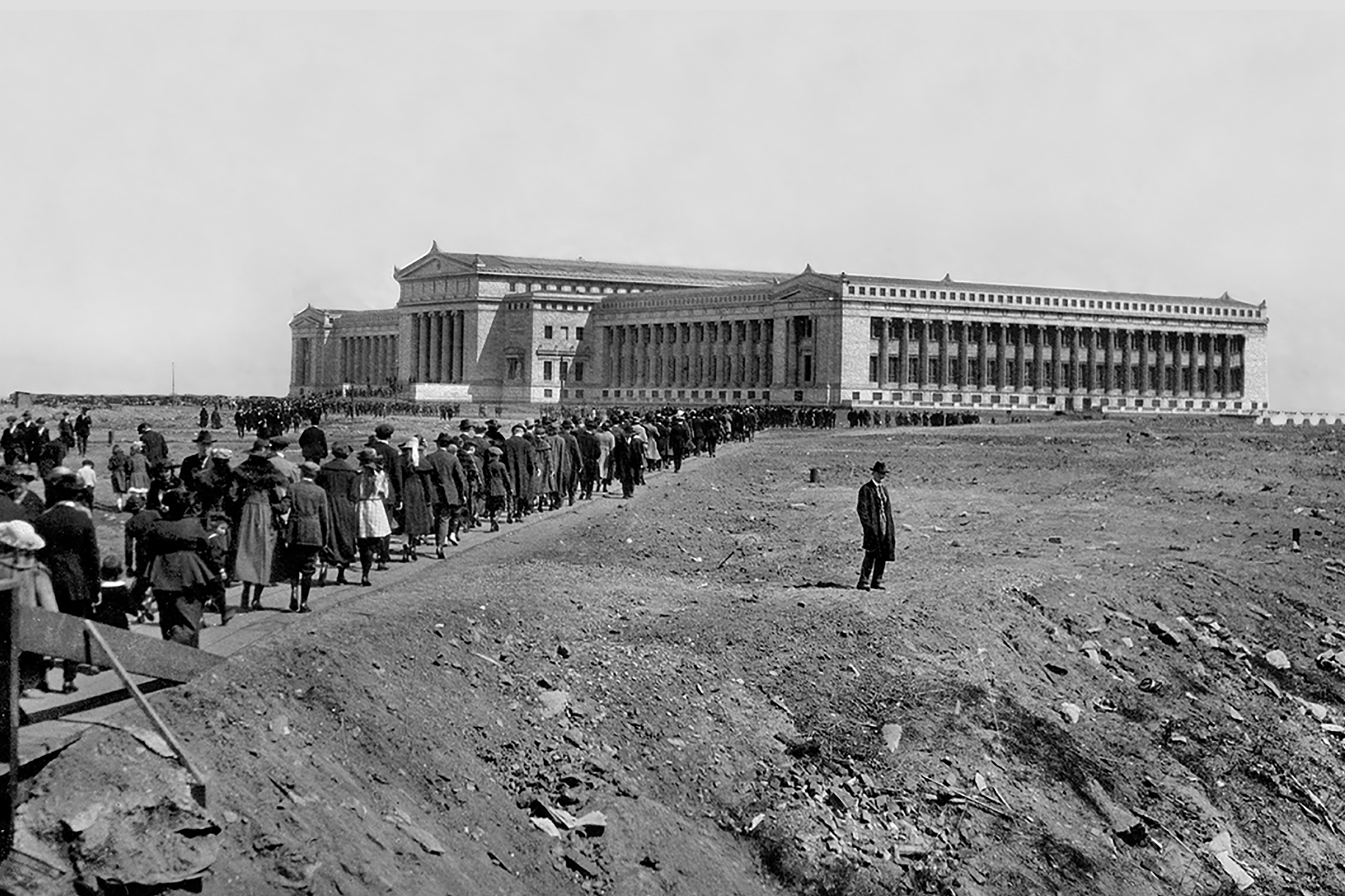 Crowds cross a wooden bridge and approach the Field Columbian Museum on opening day. A lone man stands to the side. The entire exterior view of the Museum's north and west facades are visible in the background.