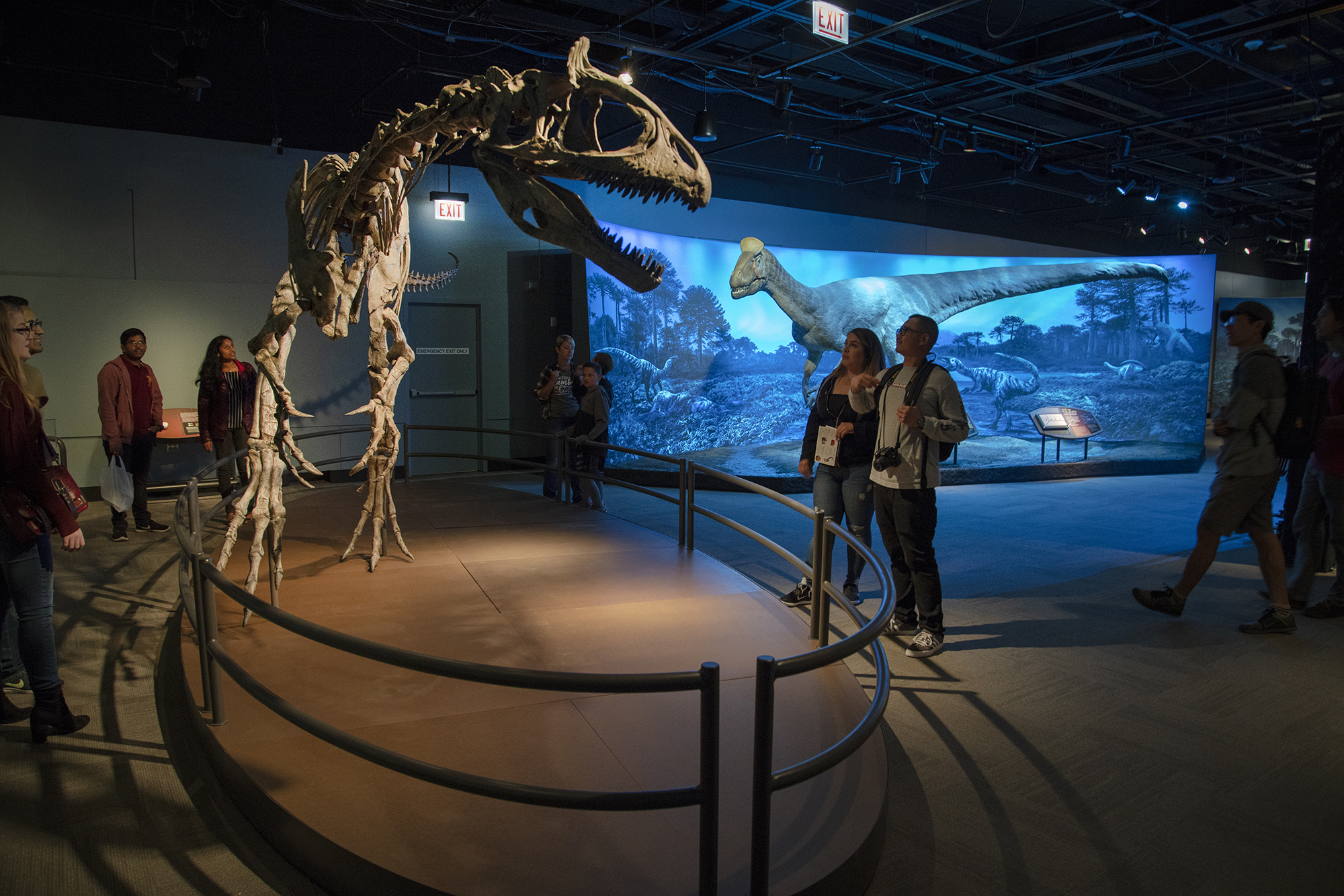 People look up at a cast of a Cryolophosaurus dinosaur skeleton on display behind a railing. The dinosaur stands on two hind legs and appears menacing, with sharp teeth. In the background, a dinosaur model is visible in a diorama under blue light.