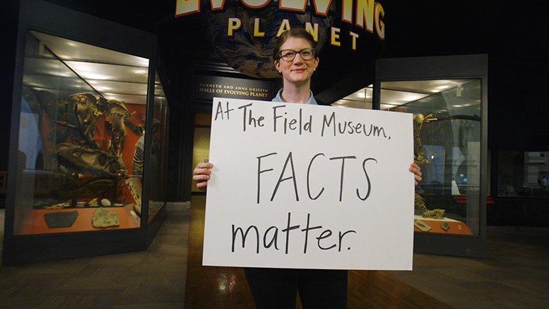 A woman holding a poster with a handwritten statement on it, standing in front of museum cases with fossils and other objects.