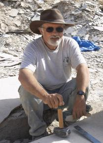Man wearing a brown hat and sunglasses, sitting amongst rock and holding a hammer
