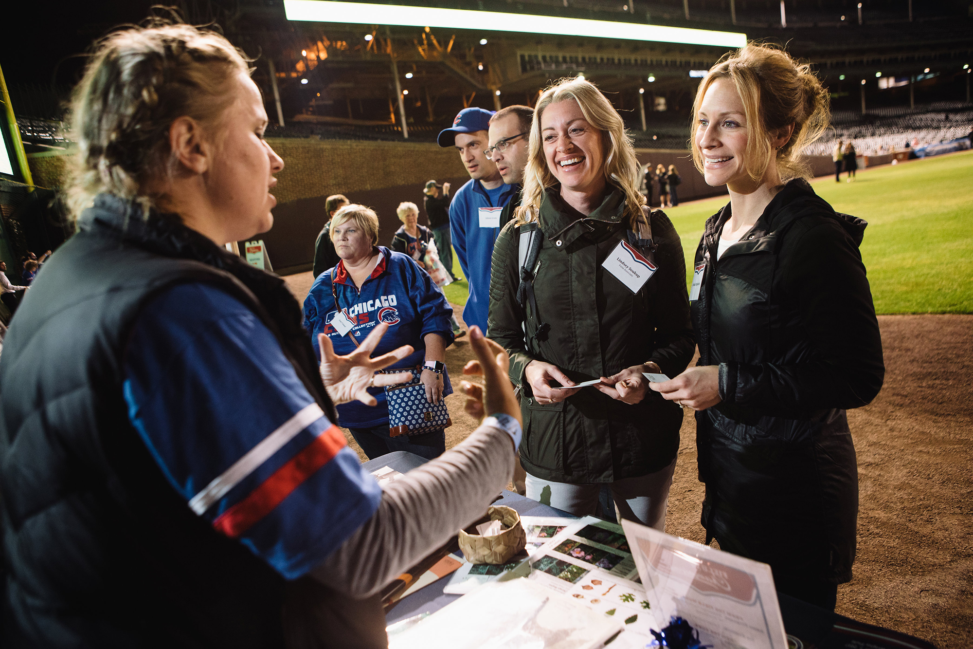 Founders' Council members gather at Wrigleyfield for an event. Two members smile and stand at a table in the field and talk with a Field scientist.
