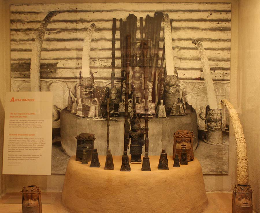 Museum display showing a number of carved objects, including elephant dusk, in front of a photograph of the same objects.