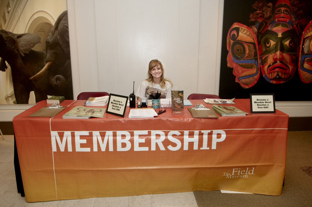 A female employee of The Field Museum sits behind a table decorated with a