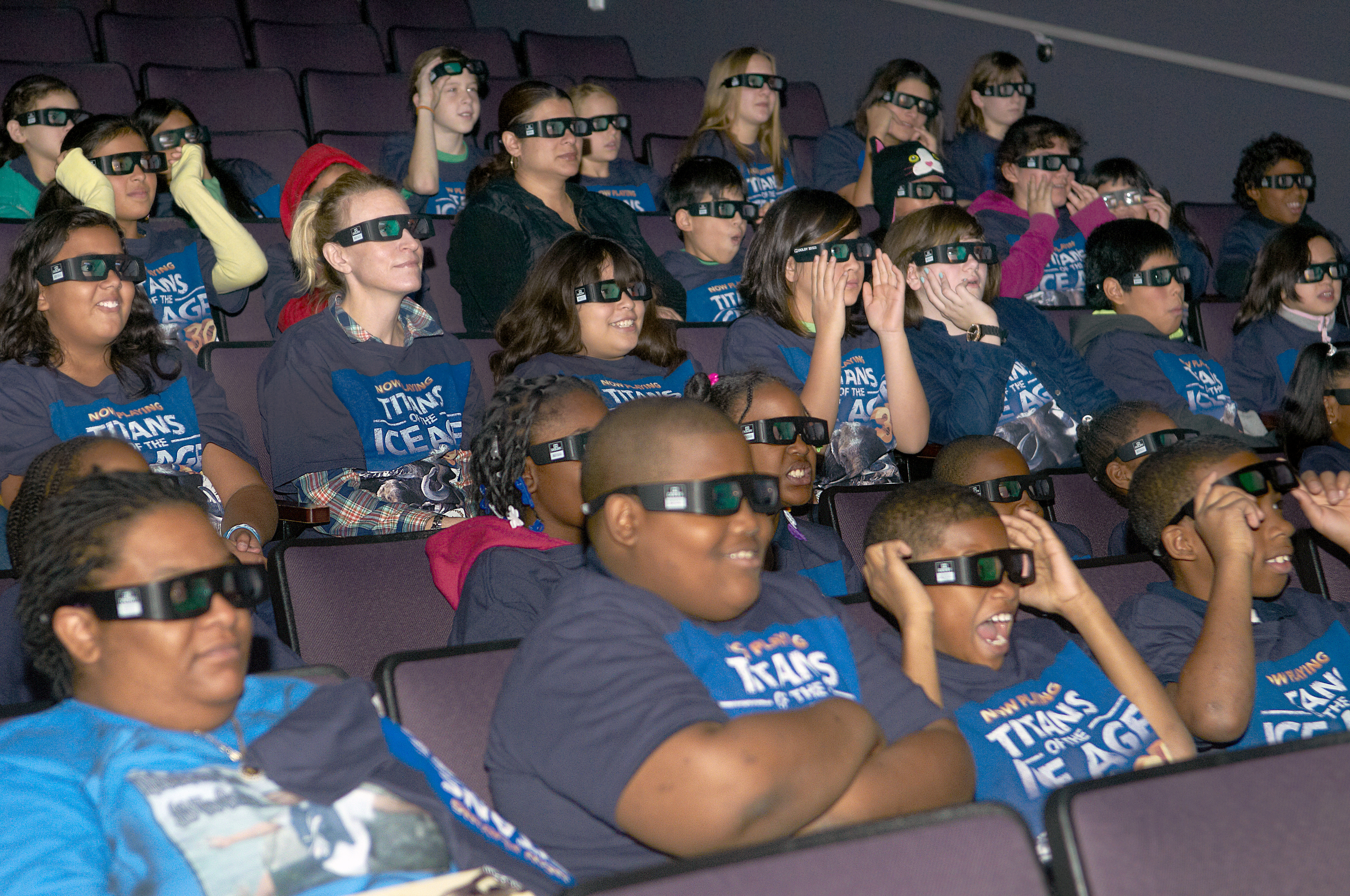 A group of students wearing black glasses sit in stadium seating to watch a 3D movie at the Field Museum.