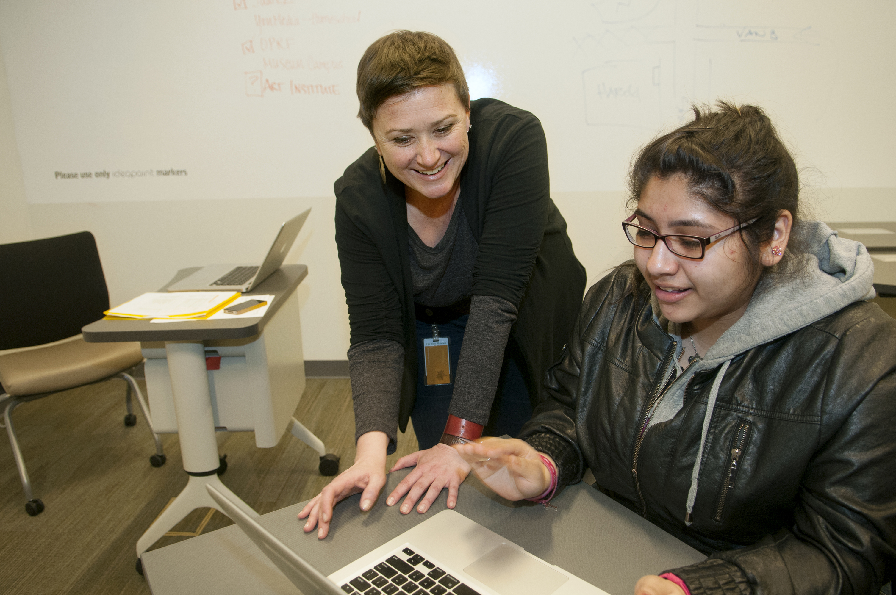 One women sits at a laptop while another one women stands close by to help. Both smile and have their hands over the keyboard.