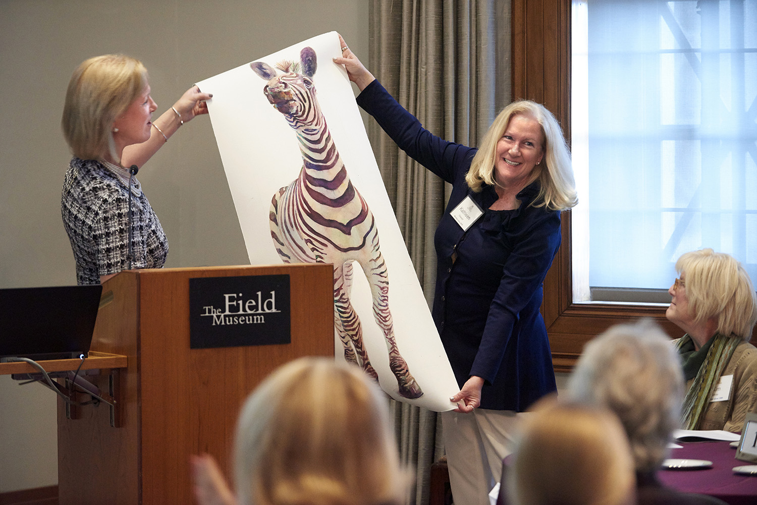 Two women hold up a painting of a zebra by Field Museum artist-in-residence Peggy McNamara, while standing behind a podium with the Museum's logo on it. Other Women's Board members, seated at tables, look on.