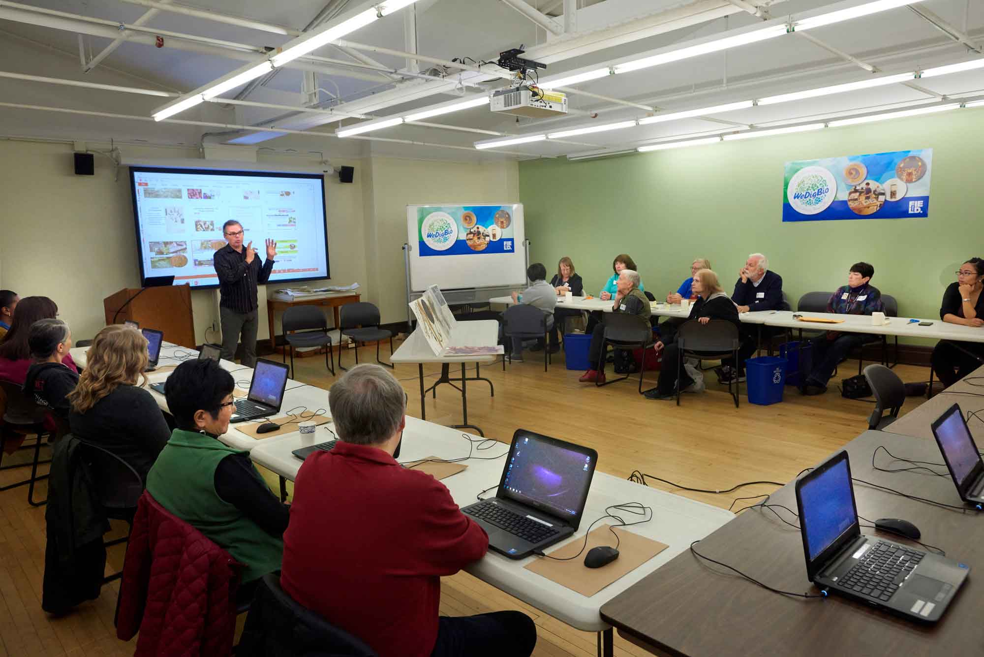 A group of volunteers gather in a classroom to digitize collections records. They sit at a set of tables arranged in a