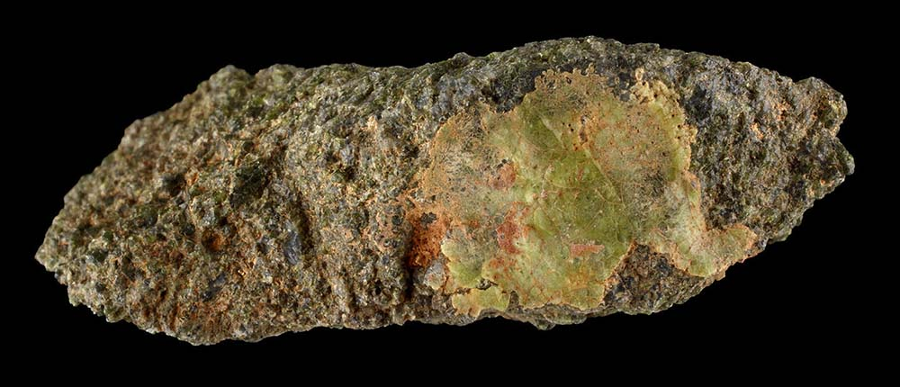An irregularly shaped stone with a rough outer surface and a shiny spot that is green and orange
