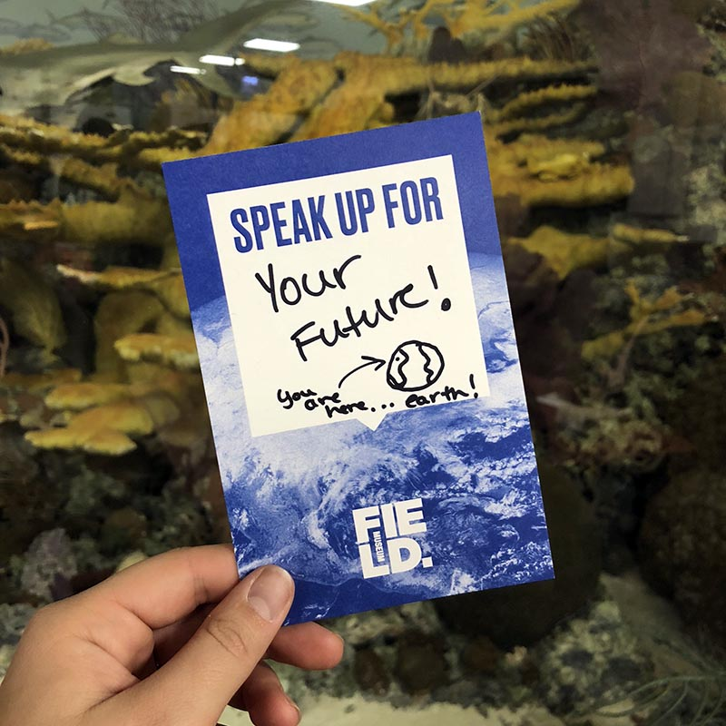 "A postcard reading ""Speak up for your future!"" held in front of a coral reef diorama."