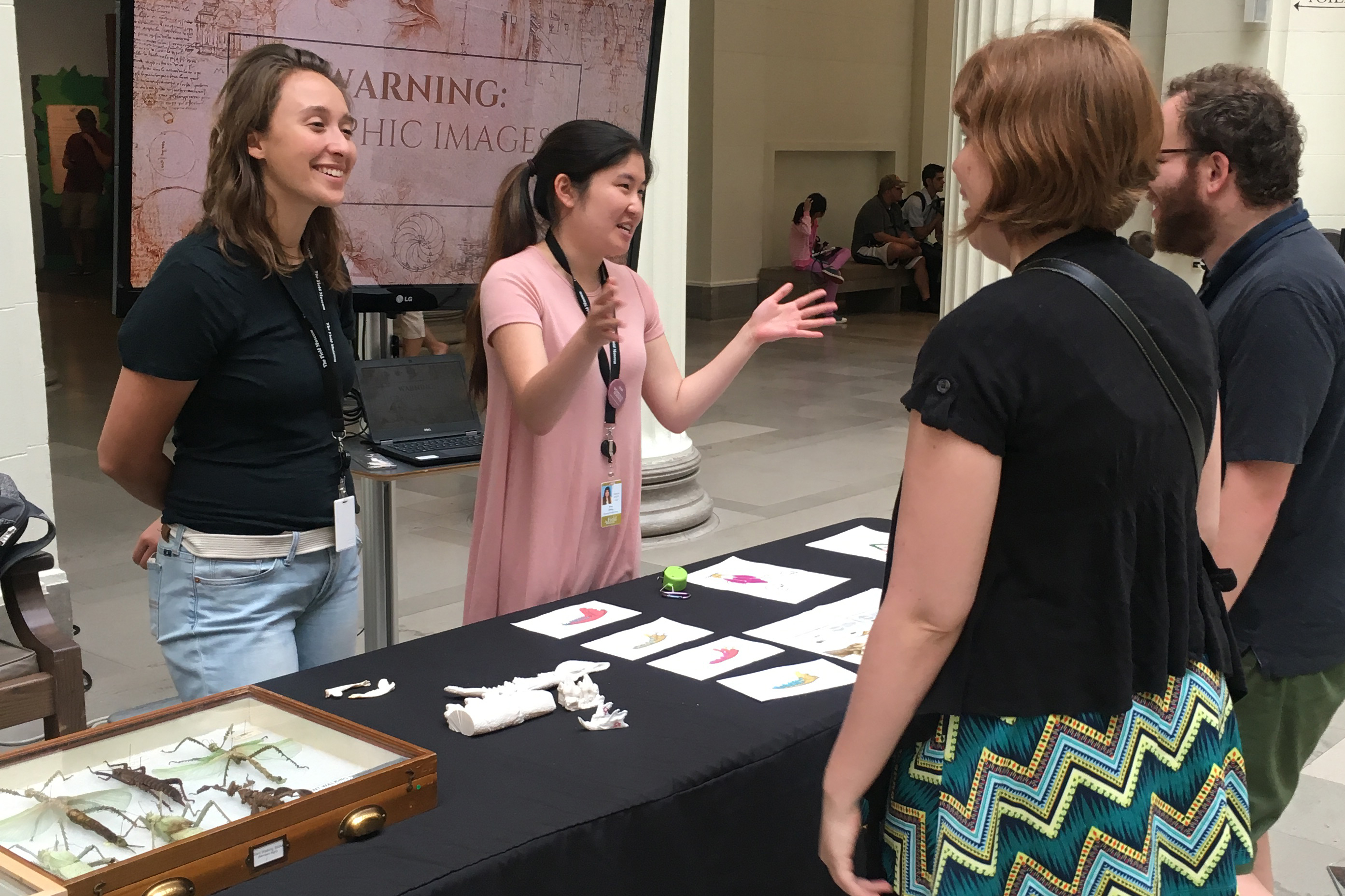 Two interns stand behind a table displaying objects from the Field Museum's collection. One speaks with the two people in front of her, gesturing as if she's showing the size of something.