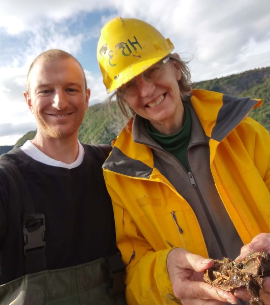 A man and a woman in waterproof gear smiling for the camera. The woman wears a yellow hard hat and is holding something that looks like a piece of wood.