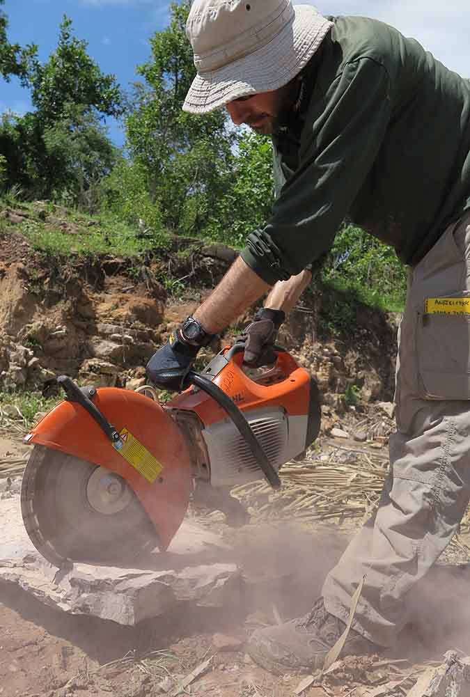 A man outside in a dry area using a circular saw to cut rock
