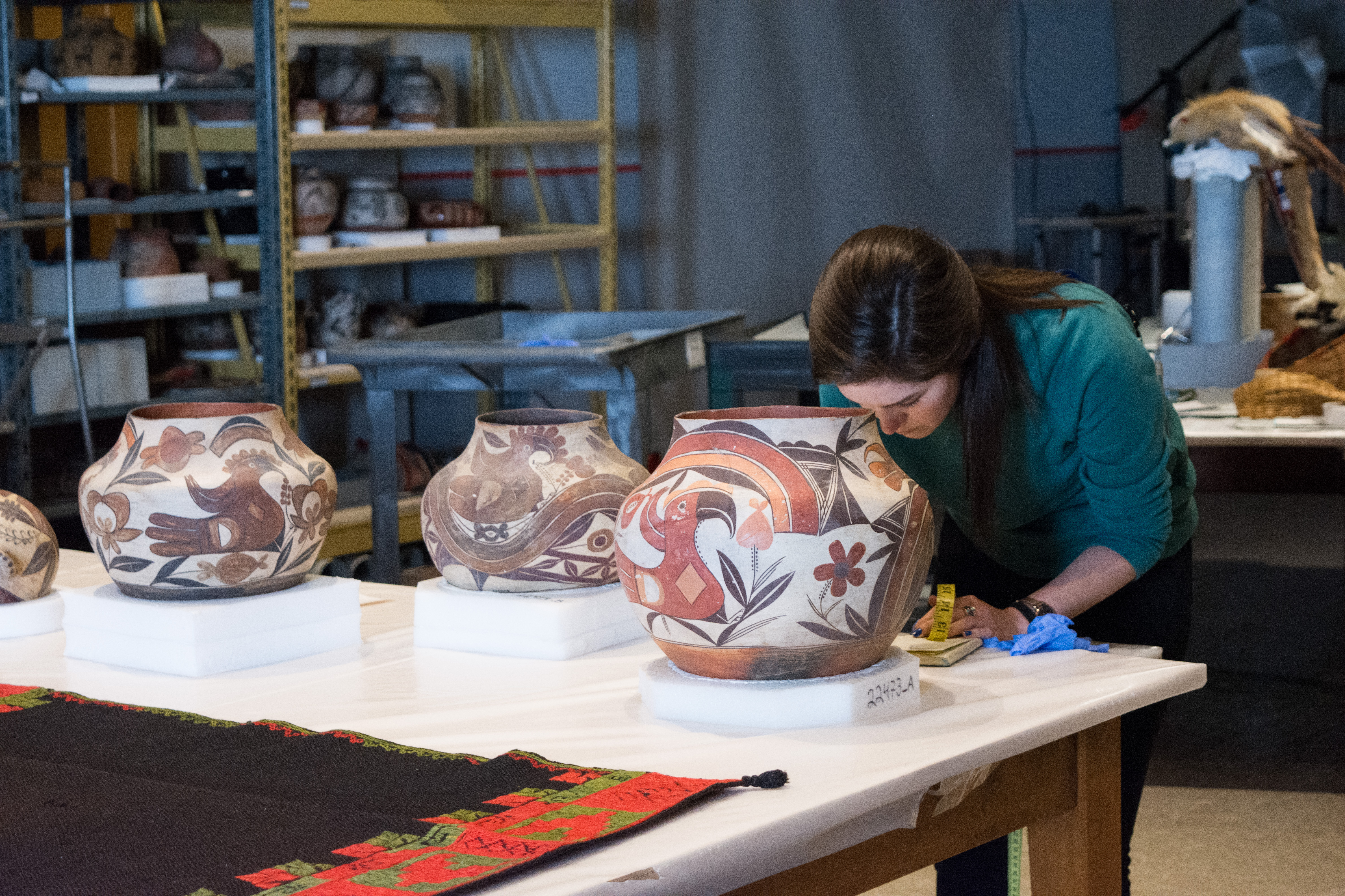 A woman stands behind a table with three large, painted pots. She holds a measuring tape and leans over the table to write something down.