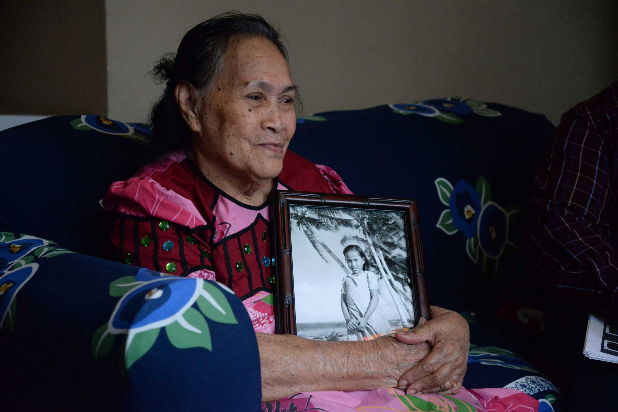 Sitting on a couch, Mojina Mote holds a framed photo of herself as a young girl.