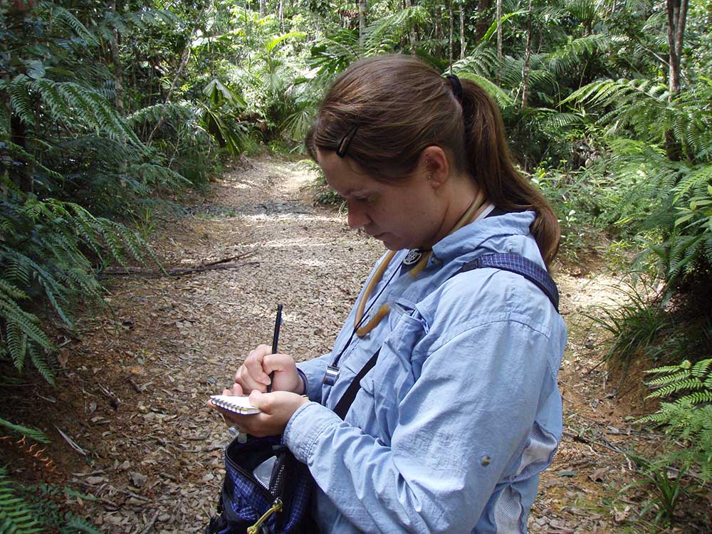 A woman in a jungle-like setting taking notes on a small notepad