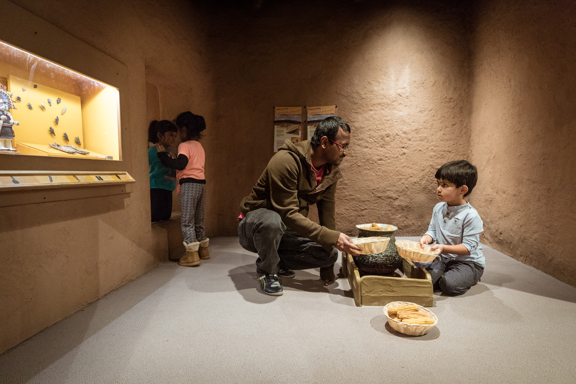Inside a recreated pueblo in the Crown Family PlayLab, a child and an adult play with baskets holding fake corn. Two girls stand in the doorway nearby.
