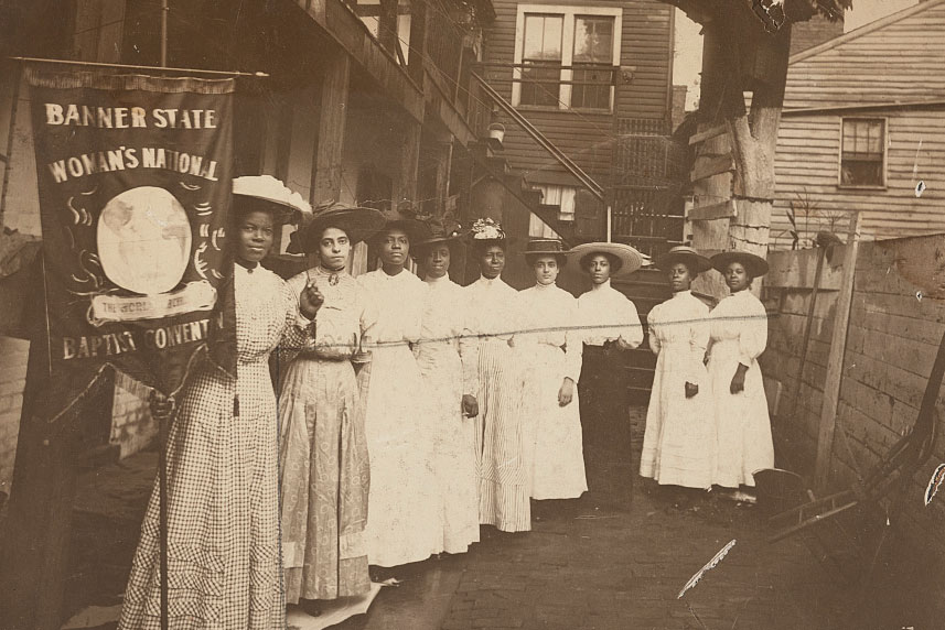 A group of African American women suffragists pose for a photo. On the left, closest to the camera, Nannie Helen Burroughs holds a banner that reads,