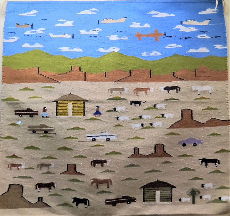 A woven rug with stylized depictions of blue sky with clouds, green and brown mountains, and farmland with cows