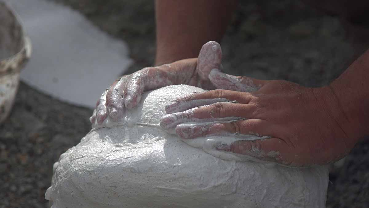 Close-up of a person's hands applying wet plaster to a mound