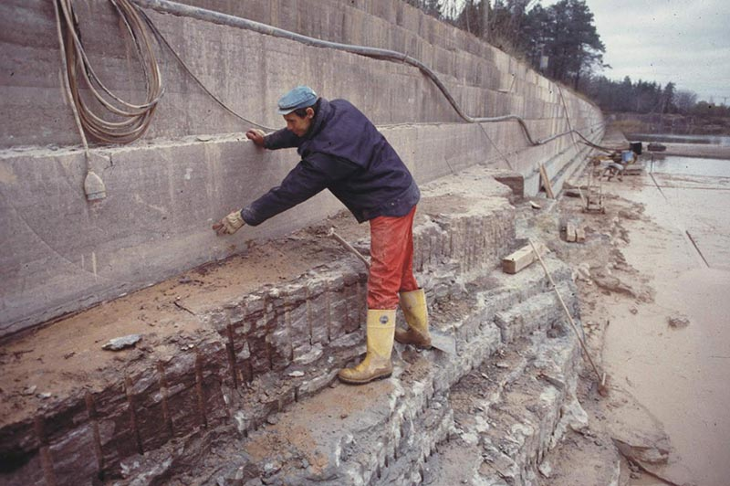 A man wearing work clothes and rain boots standing on a muddy, rocky shelf